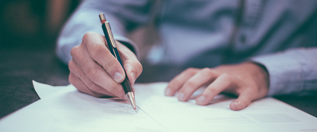 accounting and bookkeeping services man writing on piece of paper