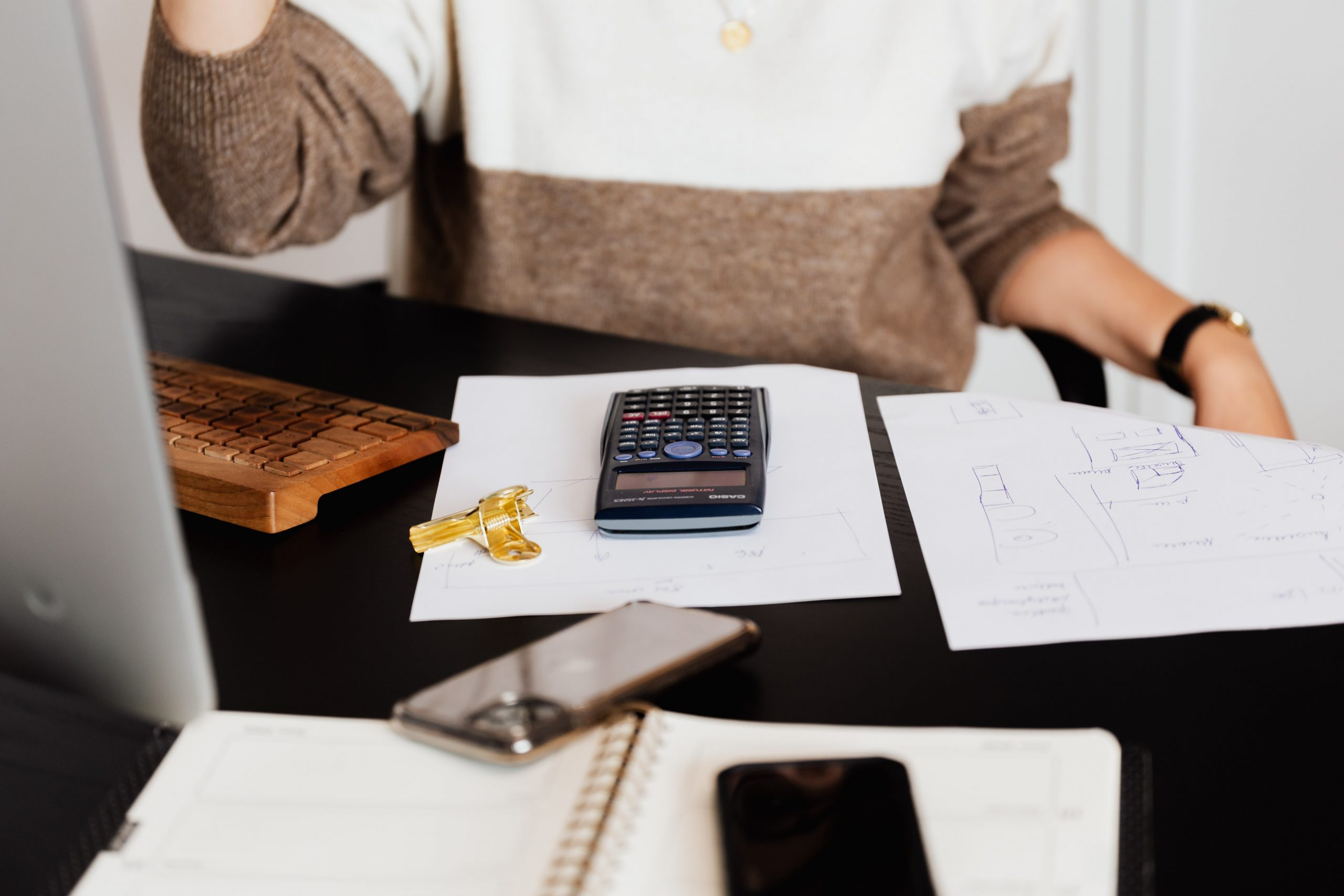accountant services woman sitting at desk with calculator
